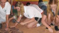 Students renovate the floor during a school renovation project in Cambodia